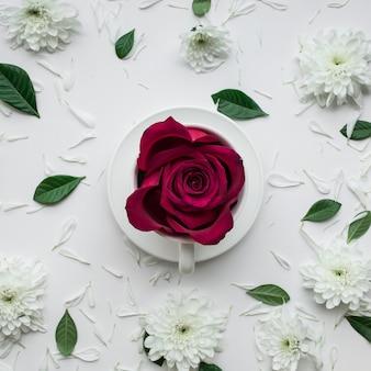 Flor rosa em xícara de café em fundo branco.