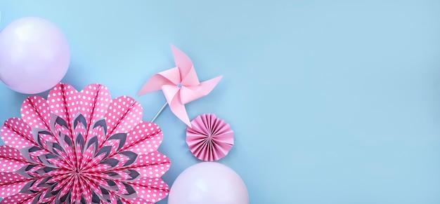 Flor rosa feita de papel moinho de vento e balões na parede azul clara Foto Premium