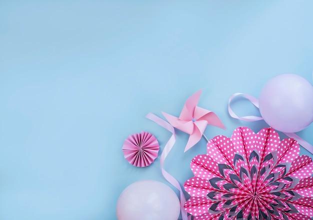 Flor rosa feita de papel moinho de vento e balões na parede azul clara