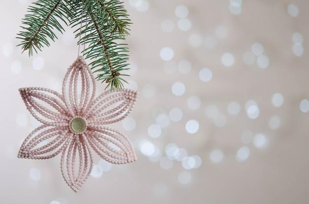 Flor rosa pendurada em um galho de árvore de natal