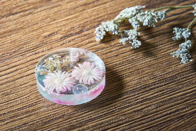 Flor rosa seca com glitter colorido em resina artesanal feita à mão sobre fundo de madeira