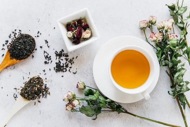 Flor rosa secas com ervas de chá em fundo de concreto