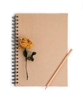 Flor rosa secas com lápis no caderno