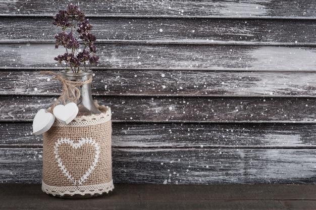 Flor seca em garrafa rústica com corações