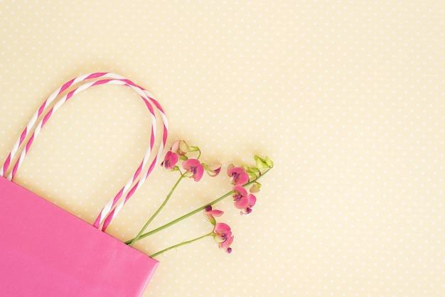 Flor selvagem roxa e sacola de compras rosa em papel amarelo.