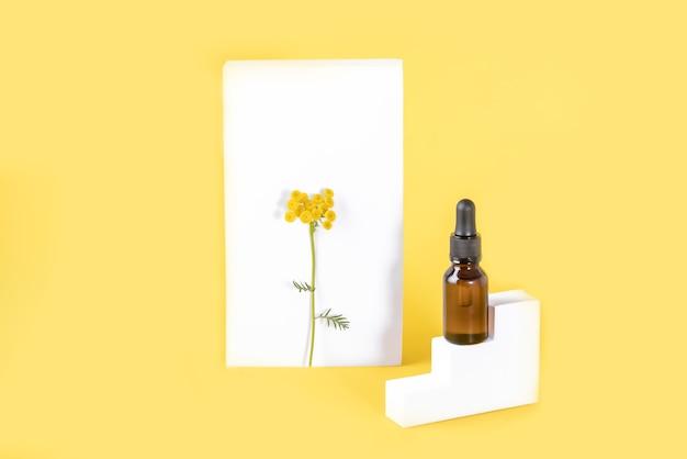 Flor tansy e um frasco de óleo tansy com formas geométricas