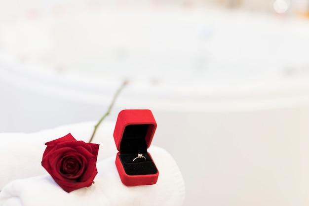 Flor, toalhas e anel na caixa de jóias perto de banheira de hidromassagem