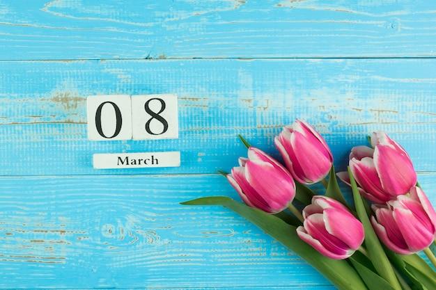 Flor tulipa rosa e 8 de março calendário sobre fundo azul mesa de madeira com espaço de cópia de texto. conceito de dia internacional do amor, igualdade e mulheres
