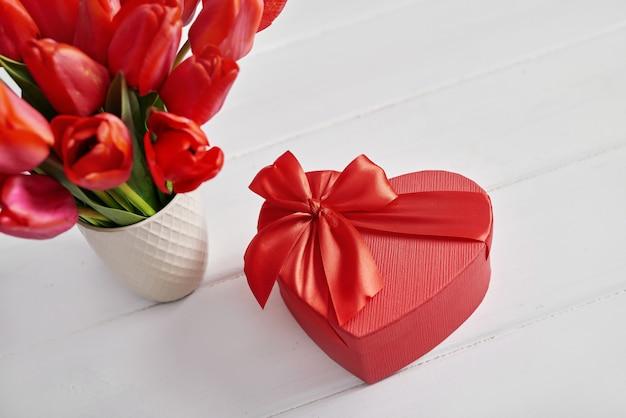 Flor tulipa vermelha e caixa de presente isolada.