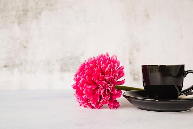 Flor vermelha com cerâmica preta xícara e pires contra parede branca