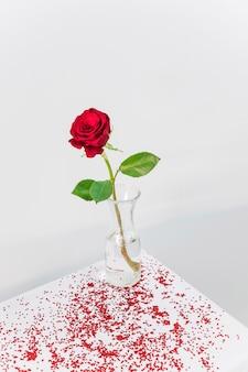 Flor vermelha fresca no vaso entre confetes na mesa