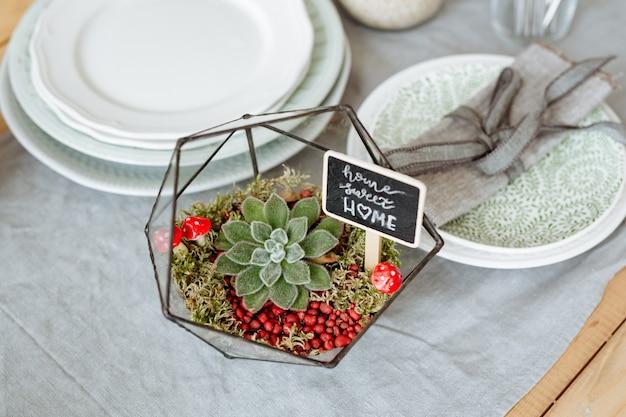 Florarium com plantas vivas na mesa da cozinha no fundo de uma mesa lindamente decorada.