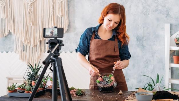 Florarium master vlog. mulher usando a câmera do smartphone para gravar o vídeo tutorial de jardinagem.