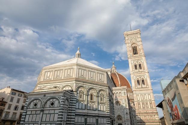 Florença, itália - 24 de junho de 2018: vista panorâmica do complexo duomo: batistério de são joão, cattedrale di santa maria del fiore e o campanário de giotto. pessoas caminham na piazza del duomo em dia de verão