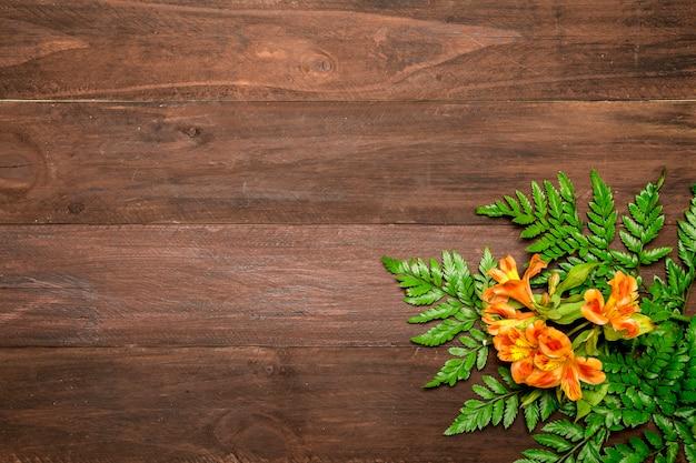 Flores alaranjadas com folhas no fundo de madeira