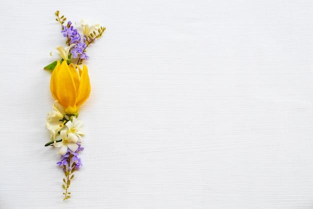 Flores amarelas arranjo de ylang ylang plano leigo estilo cartão-postal Foto Premium