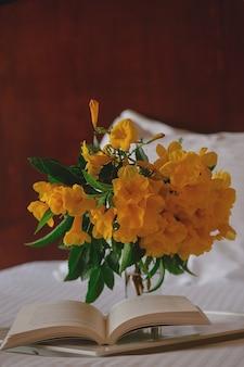 Flores amarelas com um livro em uma bandeja branca em uma cama de hotel