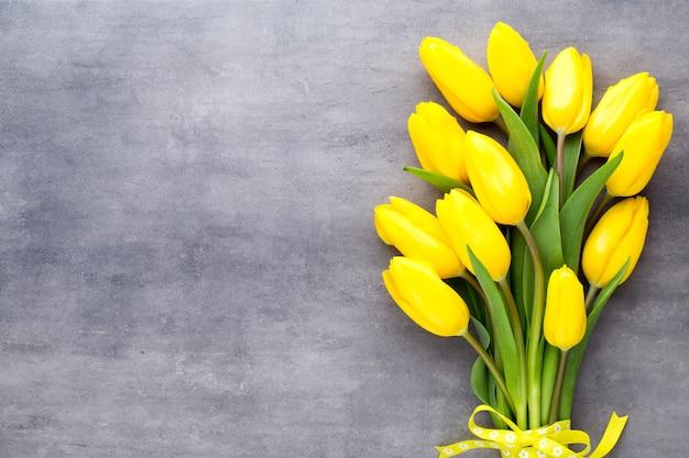 Flores amarelas da primavera, tulipa em um fundo cinza.