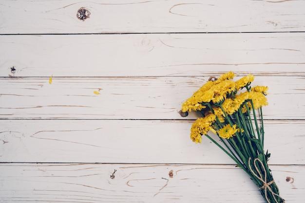 Flores amarelas de buquê, vista superior em textura de fundo branco de madeira com espaço de cópia