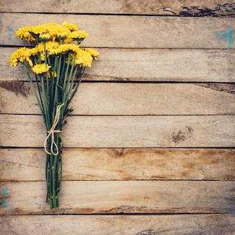 Flores amarelas de buquê, vista superior em textura de fundo de madeira com espaço de cópia