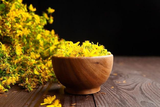 Flores amarelas de erva de são joão (hypericum perforatum) em tigela de madeira