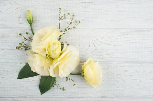 Flores amarelas de lisianthus na mesa de madeira