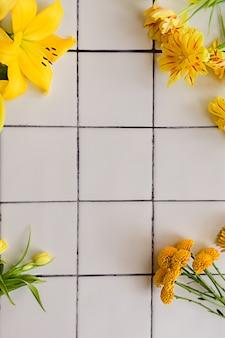 Flores amarelas diferentes em um fundo de piso de ladrilho branco