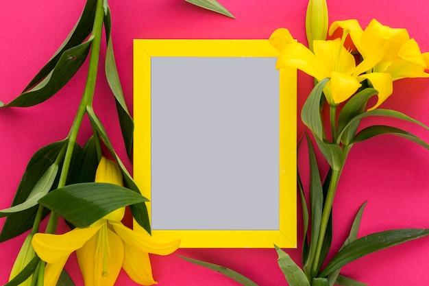Flores amarelas do lírio e moldura para retrato vazia sobre o rosa; fundo