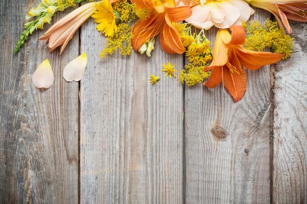Flores amarelas e laranja em fundo de madeira velha