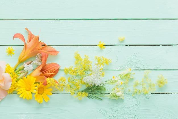 Flores amarelas e laranja em madeira verde