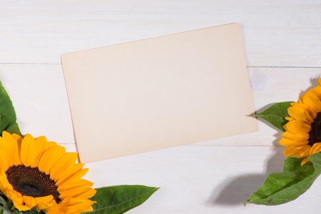 Flores amarelas e papel vazio para o seu texto em fundo de madeira