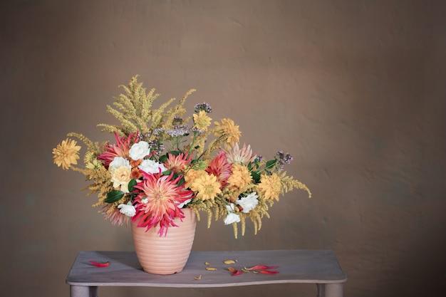 Flores amarelas e vermelhas em um vaso na prateleira vintage