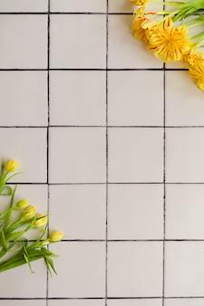 Flores amarelas em um fundo de piso de ladrilho branco