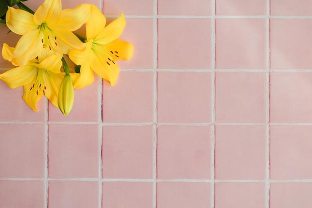 Flores amarelas em um fundo de piso de ladrilho rosa