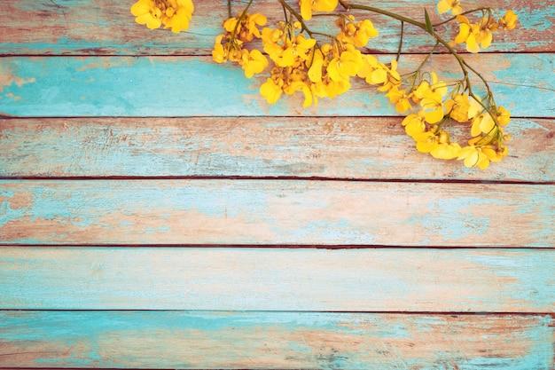 Flores amarelas fundo de madeira, tom de cor vintage
