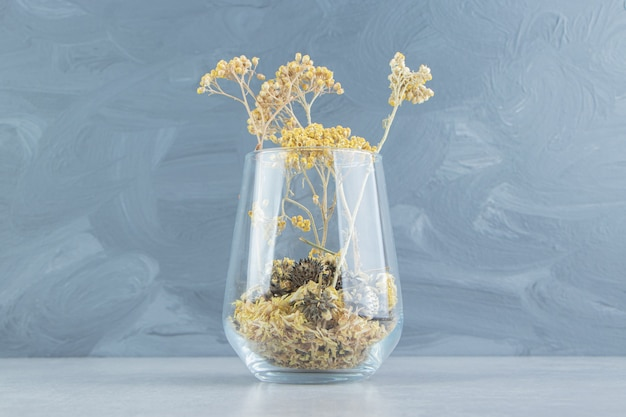 Flores amarelas secas em copo de vidro.
