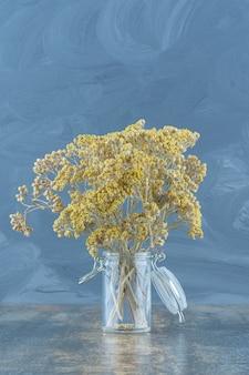 Flores amarelas secas naturais em frasco de vidro.