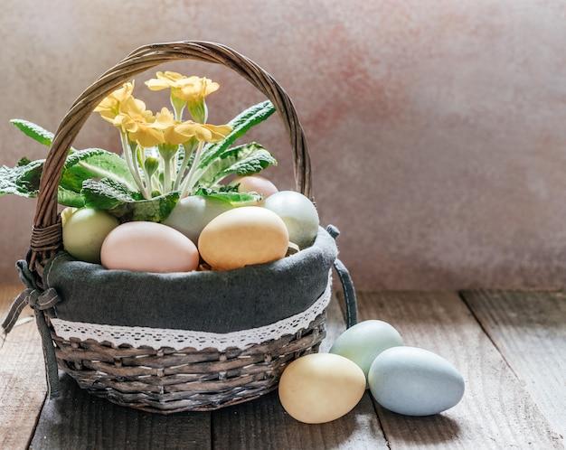 Flores amarelas violetas e ovos de páscoa na cesta na mesa de madeira escura