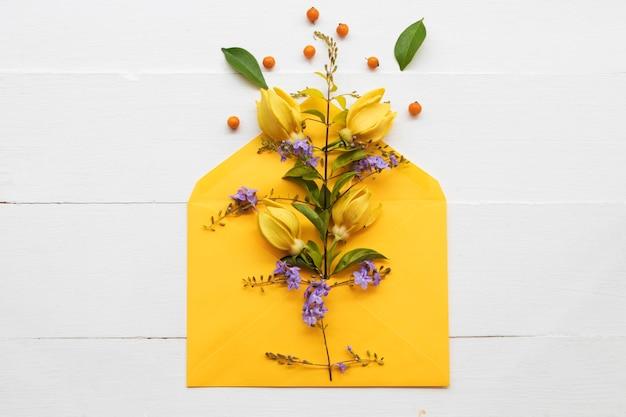 Flores amarelas ylang ylang em envelope arranjo estilo cartão postal