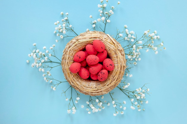 Flores ao lado da cesta com ovos para a páscoa