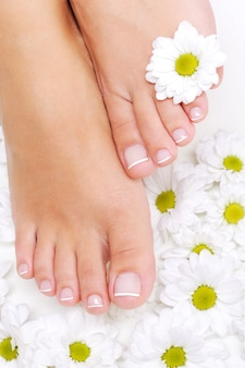 Flores ao redor de pés de mulher bem tratados com pedicure de beleza