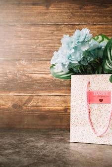 Flores artificiais no saco de presente de papel contra o pano de fundo de madeira