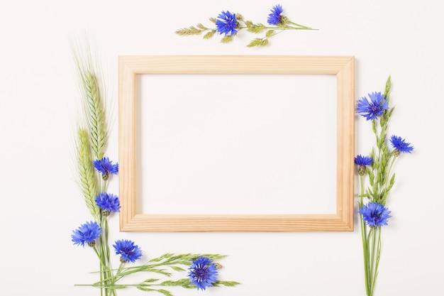 Flores azuis e cereais com moldura de madeira na superfície branca