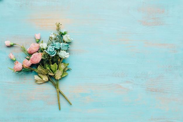 Flores azuis e cor-de-rosa com fundo de madeira do vintage.