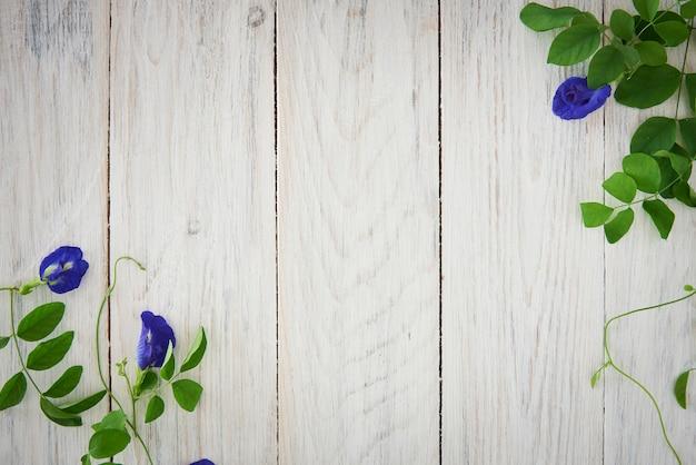 Flores azuis e fundo de cerca de madeira