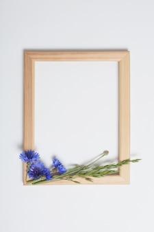 Flores azuis e moldura de madeira em fundo branco