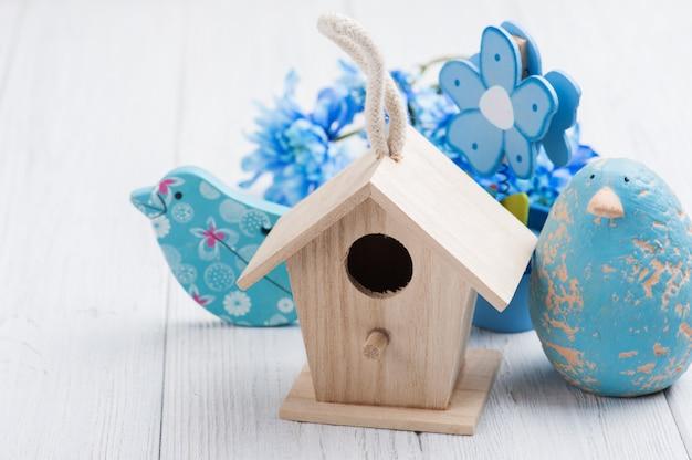 Flores azuis, pássaros de brinquedo e casa de passarinho