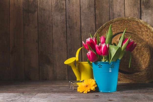 Flores bonitas com ferramentas de jardinagem e fundo de madeira