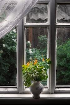 Flores brancas aves de capoeira e erva de são joão amarela em um vaso no parapeito de uma janela em uma vila no verão
