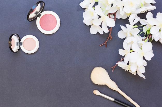 Flores brancas; blush rosa e bege com dois pincel de maquiagem em fundo cinza